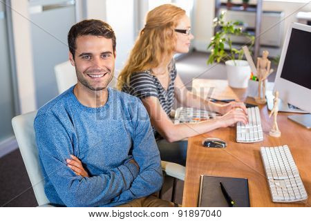 Smiling partners sitting together at desk in the office