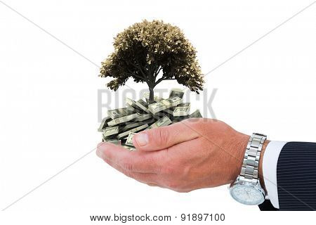 Businessman in suit offering handshake against tree with lots of leaves growing