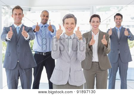 Business team smiling at camera showing thumbs up in the office