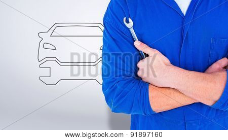 Male mechanic holding spanner on white background against grey vignette