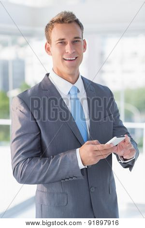 Businessman texting with his smartphone in the office