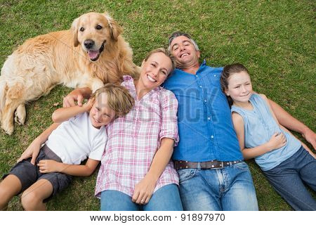 Happy family smiling at the camera with their dog on a sunny day