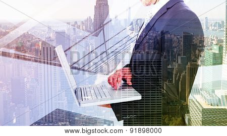 Businessman holding laptop against city skyline