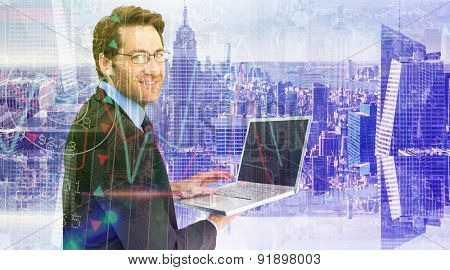 Smiling businessman using a laptop against room with large window looking on city