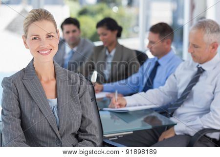 Businesswoman smiling at camera with colleagues behind in the office