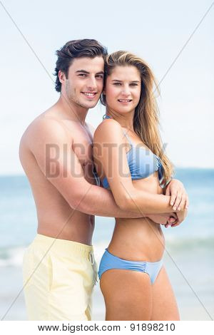 Happy couple in swimsuit looking at camera and embracing at the beach