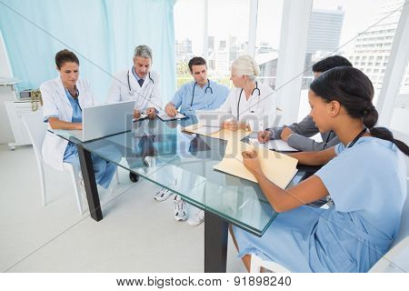 Male and female doctors using laptop in the medical office