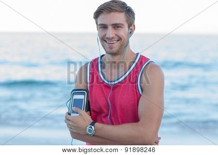 Handsome runner looking at camera at the beach