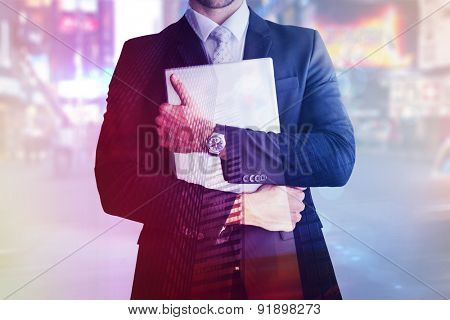 Mid section of businessman holding computer against low angle view of skyscrapers at sunset