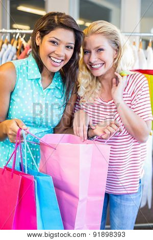 Smiling friends holding shopping bags in clothes store