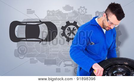 Mechanic working on tire against grey vignette