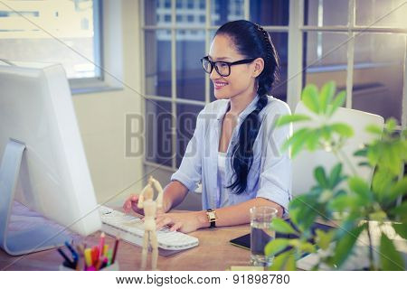 Happy young designer working at desk in creative office