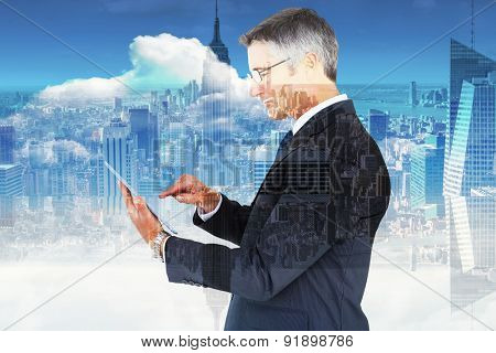 Mid section of a businessman touching tablet against room with large window looking on city