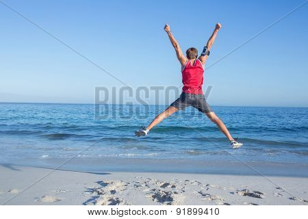 Handsome man jumping at the beach