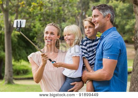 Happy family using a selfie stick in the park on a sunny day