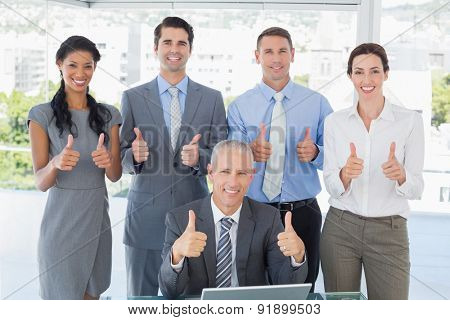 Smiling business team standing thumbs up in the office