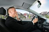 pic of yawn  - Portrait Of A Young Businessman Yawning While Driving Car - JPG