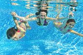 stock photo of family vacations  - Happy smiling family underwater in swimming pool - JPG
