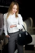foto of early 20s  - Cool attractive girl wearing modern office style outfit looking at watch checking time holding one hand in her pocket waiting - JPG