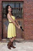 image of handgun  - Beautiful young woman holding a loaded handgun - JPG