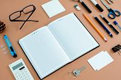 image of neat  - Assortment of Office Supplies Neatly Organized Around Note Book Open to Blank Page on Desk Top Surface - JPG