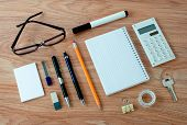 stock photo of neat  - High Angle View of Office or School Supplies Arranged Neatly Around Notebook with Blank Page on Wooden Desk Surface - JPG