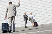 picture of carry-on luggage  - Rear view of businessman carrying luggage waving hand to colleagues - JPG