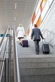 picture of upstairs  - Full length rear view of businesspeople with luggage moving upstairs in railroad station - JPG