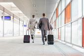 stock photo of carry-on luggage  - Full length rear view of businessmen with luggage running on railroad platform - JPG