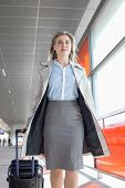 foto of carry-on luggage  - Young businesswoman with luggage walking in railroad station - JPG