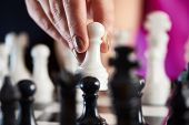 foto of chessboard  - Hand with white pawn over chessboard closeup - JPG