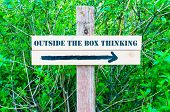 stock photo of thinking outside box  - OUTSIDE THE BOX THINKING written on Directional wooden sign with arrow pointing to the right against green leaves background - JPG