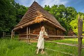 stock photo of national costume  - Young woman in ukrainian national costume near old wooden house  - JPG