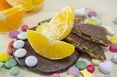 stock photo of bonbon  - Fresh orange biscuits and colorful bonbons on a wooden table - JPG