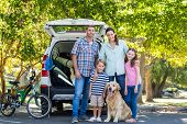 stock photo of road trip  - Happy family getting ready for road trip on a sunny day - JPG