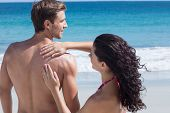 picture of sun-tanned  - Pretty brunette putting sun tan lotion on her boyfriend at the beach - JPG