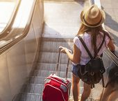 picture of escalator  - Young girl with suitcase down the escalator - JPG