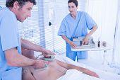 pic of defibrillator  - Medical team resuscitating a man with a defibrillator in hospital room - JPG