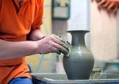 foto of loam  - On a rotating pottery wheel wizard manually manufactures ceramic vase - JPG