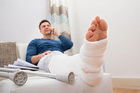 pic of fracture  - Man With Fractured Leg Sitting On Sofa Talking On Cellphone - JPG