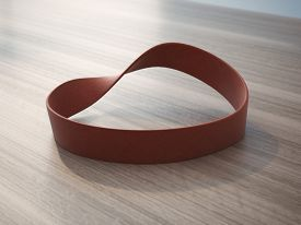 pic of rubber band  - Twisted red rubber wrist band on wooden table - JPG
