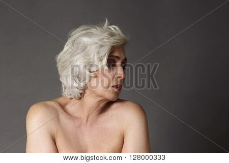 Beautiful woman with bare shoulders studio portrait. Fashion model lady posing in studio for photographer.