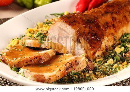 A juicy fresh pork loin roast sliced on a plate.