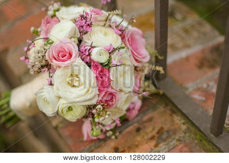 Colorful bridal bouquet on a brick wall