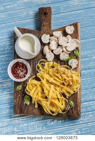 Raw ingredients for cooking pasta with mushroom cream sauce - pasta mushrooms cream spices. On rustic wooden board on blue background