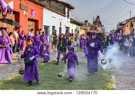 Antigua Guatemala - March 24 2016: Local boys & man dressed as penitents cleanse air with incense smoke in front of Holy Thursday procession with Virgin Mary. Agua volcano is behind in town with most famous Holy Week celebrations in Latin America.