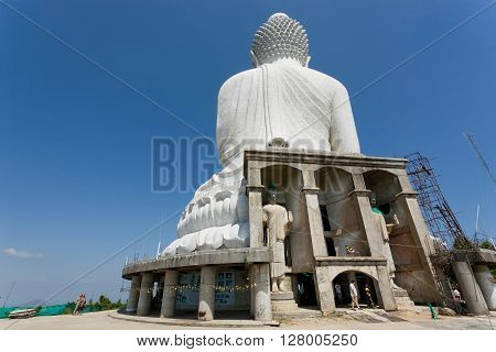 PHUKET, THAILAND - FEB 6, 2016: Construction in progress of the Big Buddha Temple with giant marble statue and tourists on February 6, 2016. First written mention about the buddhist monastery belongs to 1837