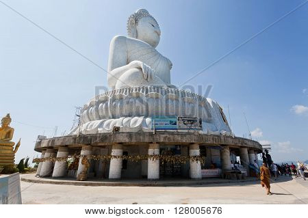 PHUKET, THAILAND - FEB 6, 2016: Buddhist monk going to pray at the Big Buddha Temple from white marble on February 6, 2016. First written mention about the buddhist monastery belongs to 1837