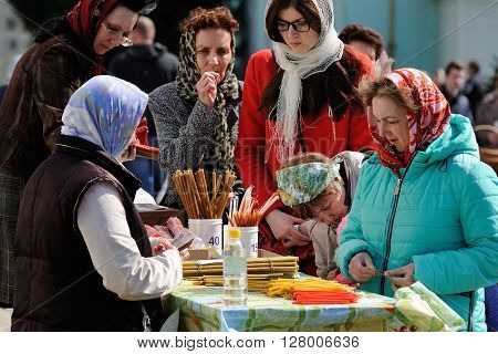 Orel Russia - April 30 2016: Paschal blessing of Easter baskets in Orthodox church. Women buying church candles closeup