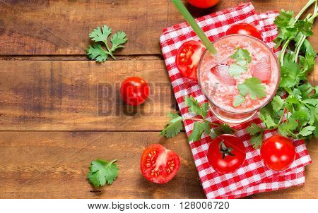 Tomato smoothie, fresh tomatoes and cilantro on wooden dark background. Top view